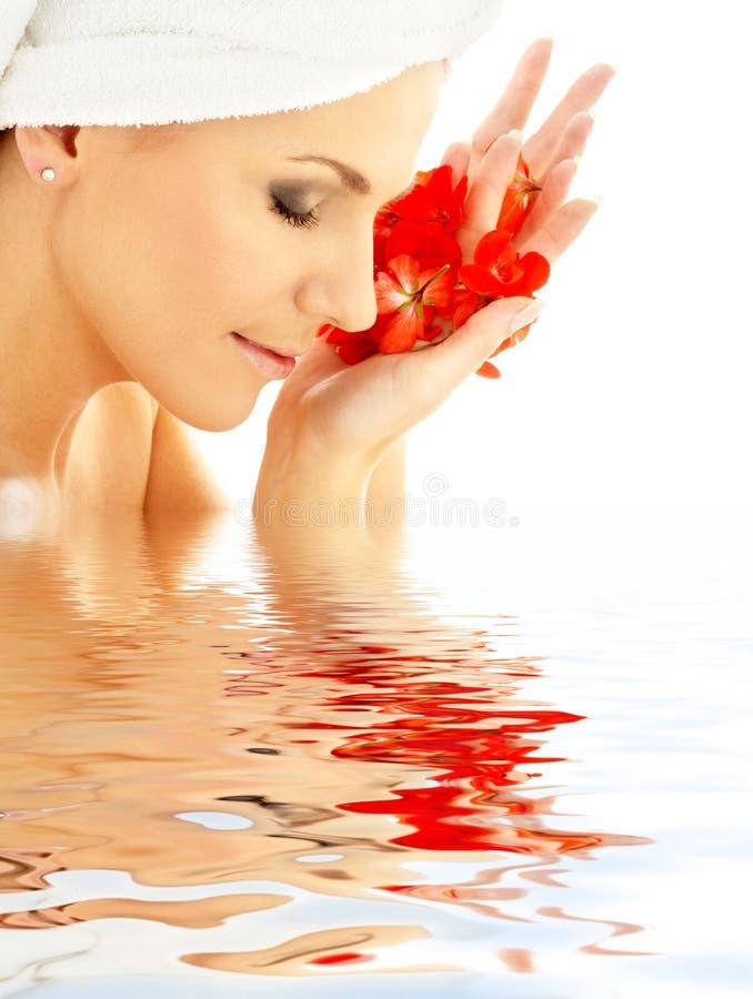 Señora con los pétalos rojos en agua fotos de archivo libres de regalías