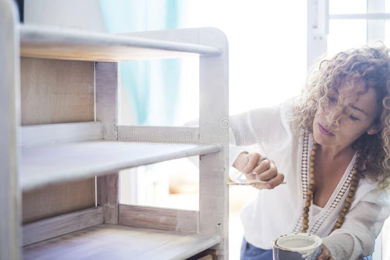 Señora concentrada hermosa en el trabajo en casa restyling y que repara un viejo furnitre con la pintura blanca hágalo usted mism fotos de archivo libres de regalías