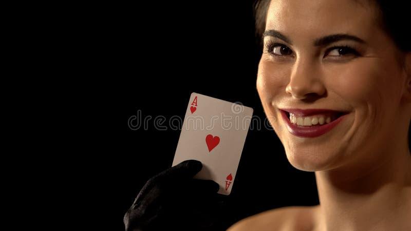 Señora coqueta que muestra el as de la tarjeta de los corazones y que sonríe a la cámara, fondo negro fotos de archivo libres de regalías