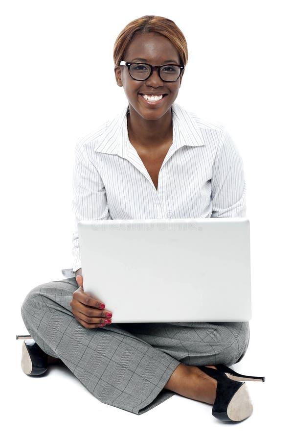 Señora corporativa asentada en el suelo que trabaja en la computadora portátil imagenes de archivo