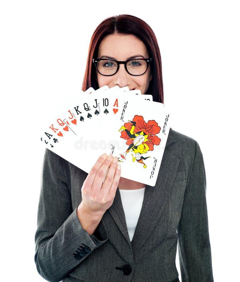 Señora corporativa que oculta su sonrisa con las tarjetas que juegan imágenes de archivo libres de regalías