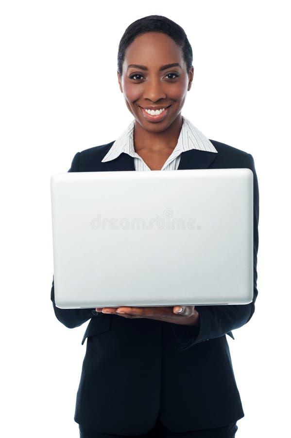 Señora corporativa que sostiene el ordenador portátil a estrenar fotografía de archivo libre de regalías