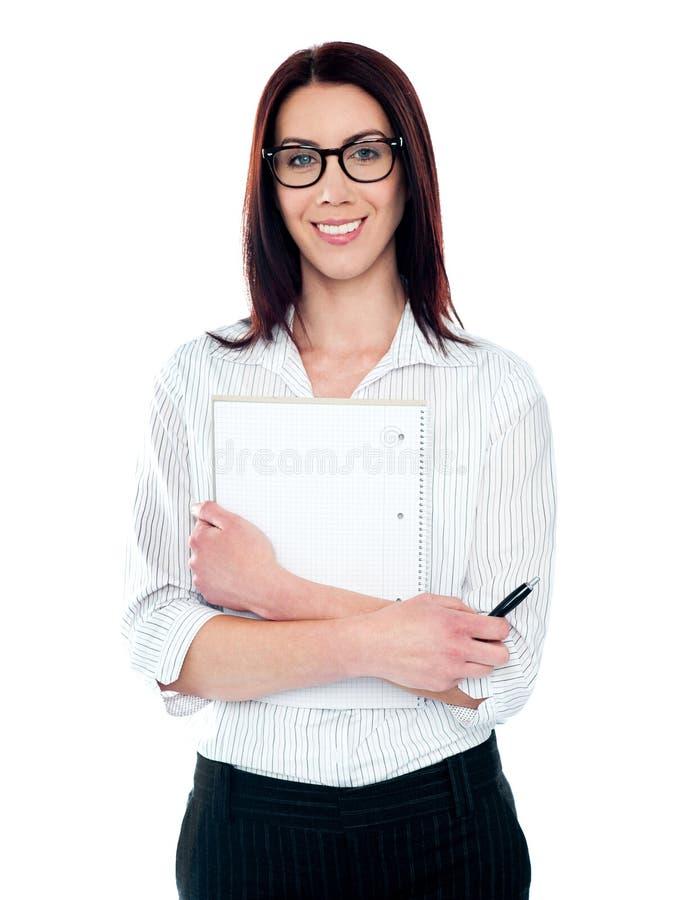 Señora corporativa que sostiene la libreta y la pluma virales imagenes de archivo