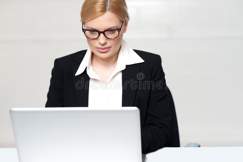 Señora corporativa que trabaja en la computadora portátil imagen de archivo libre de regalías