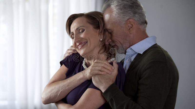Señora de abrazo masculina mayor de detrás, ambo sonrisa, matrimonio armonioso foto de archivo libre de regalías