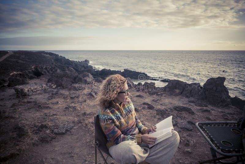 Se?ora de la Edad Media con sentarse rubio del pelo rizado y del libro de papel al aire libre delante de la costa del oc?ano que  foto de archivo