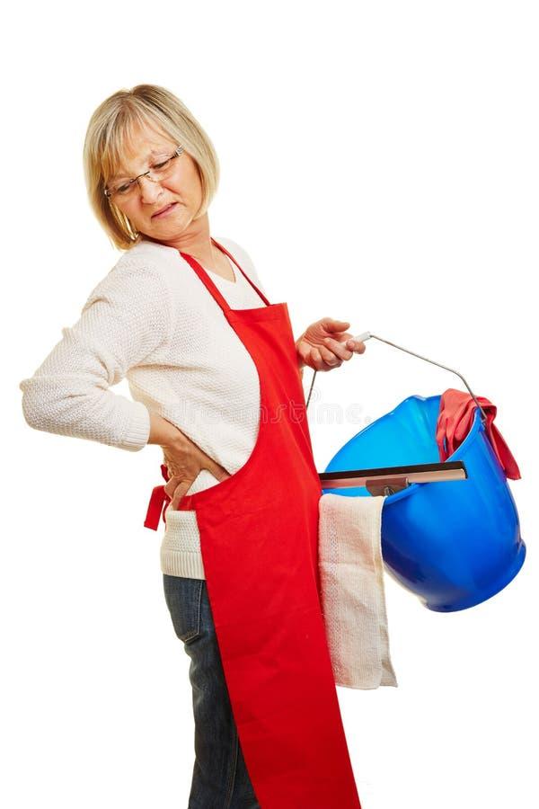 Señora de la limpieza con dolor de espalda foto de archivo libre de regalías