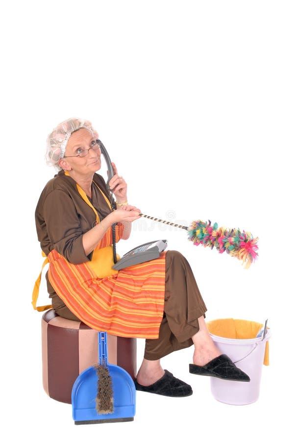 Señora de la limpieza en el teléfono fotos de archivo libres de regalías