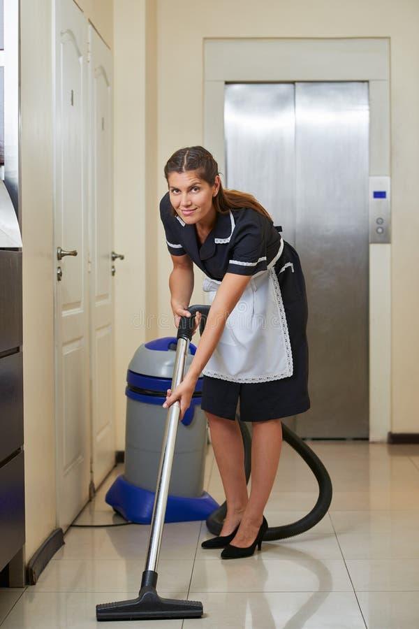 Señora de la limpieza en hotel con el aspirador imagen de archivo