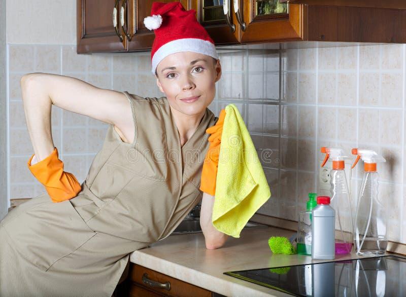 Señora de la limpieza joven en la cocina foto de archivo libre de regalías
