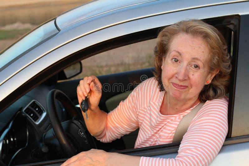 Señora de mirada insegura que lleva a cabo llaves del coche imagen de archivo