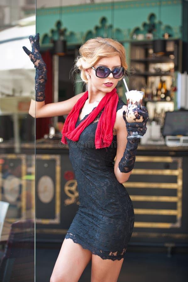 Señora de moda con el vestido negro corto y bufanda y tacones altos rojos, tiro al aire libre del cordón Blonde de pelo corto atr foto de archivo libre de regalías