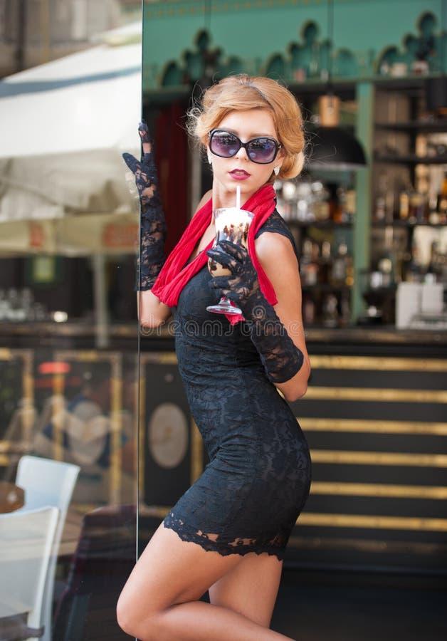Señora de moda con el vestido negro corto y bufanda y tacones altos rojos, tiro al aire libre del cordón Blonde de pelo corto atr imagenes de archivo