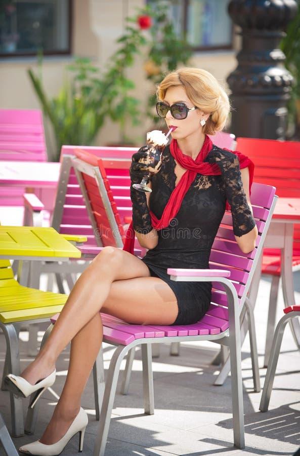 Señora de moda con poco vestido negro y bufanda roja que se sientan en silla en el restaurante, tiro al aire libre en día soleado imagen de archivo libre de regalías