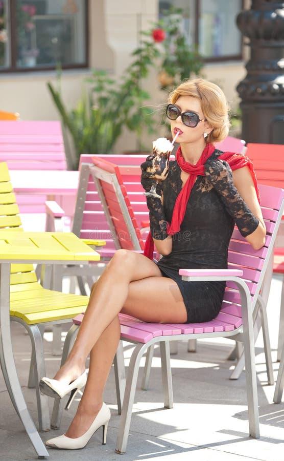 Señora de moda con poco vestido negro y bufanda roja que se sientan en silla en el restaurante, tiro al aire libre en día soleado fotos de archivo libres de regalías