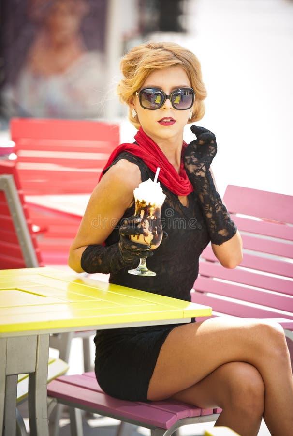 Señora de moda con poco vestido negro y bufanda roja que se sientan en silla en el restaurante, tiro al aire libre en día soleado fotografía de archivo