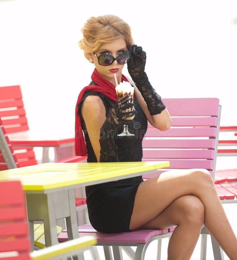 Señora de moda con poco vestido negro y bufanda roja que se sientan en silla en el restaurante, tiro al aire libre en día soleado imagenes de archivo