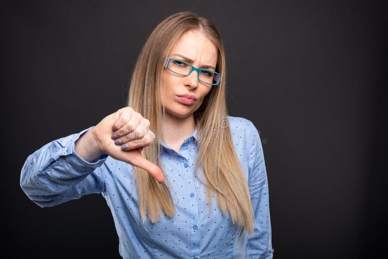 Señora del negocio que lleva los vidrios azules que muestran el pulgar abajo imágenes de archivo libres de regalías