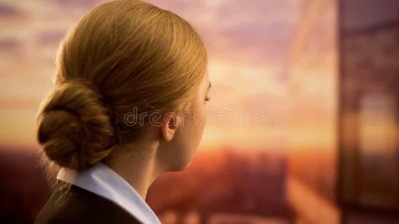 Señora del negocio que mira la puesta del sol, soñando con vacaciones, falta de tiempo para los viajes fotografía de archivo libre de regalías