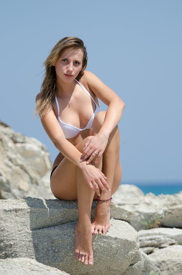 Señora delgada con el cuerpo excepcional que se sienta en rocas fotografía de archivo libre de regalías