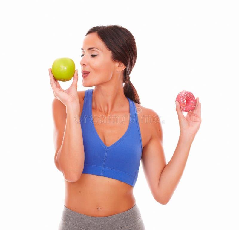 Señora deportiva que elige la manzana sobre el buñuelo fotografía de archivo libre de regalías