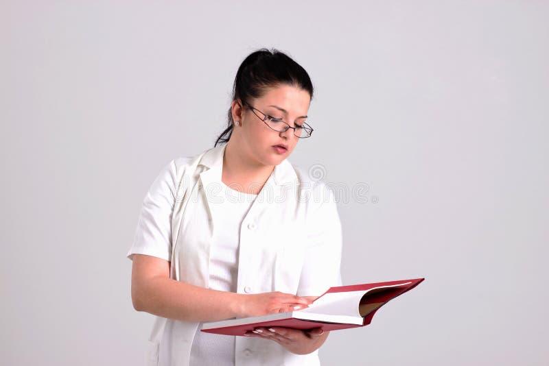 Señora Doctor en la ropa de Clinicall está leyendo diagnostica el libro imagen de archivo libre de regalías