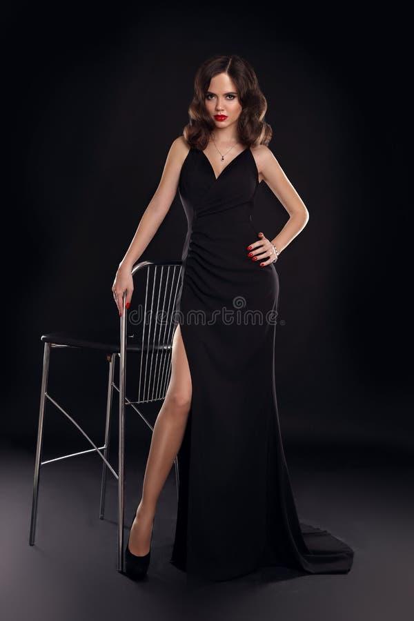 Señora elegante en el vestido sexy largo con la presentación ondulada retra del peinado aislado en fondo del negro del estudio Mu fotos de archivo libres de regalías
