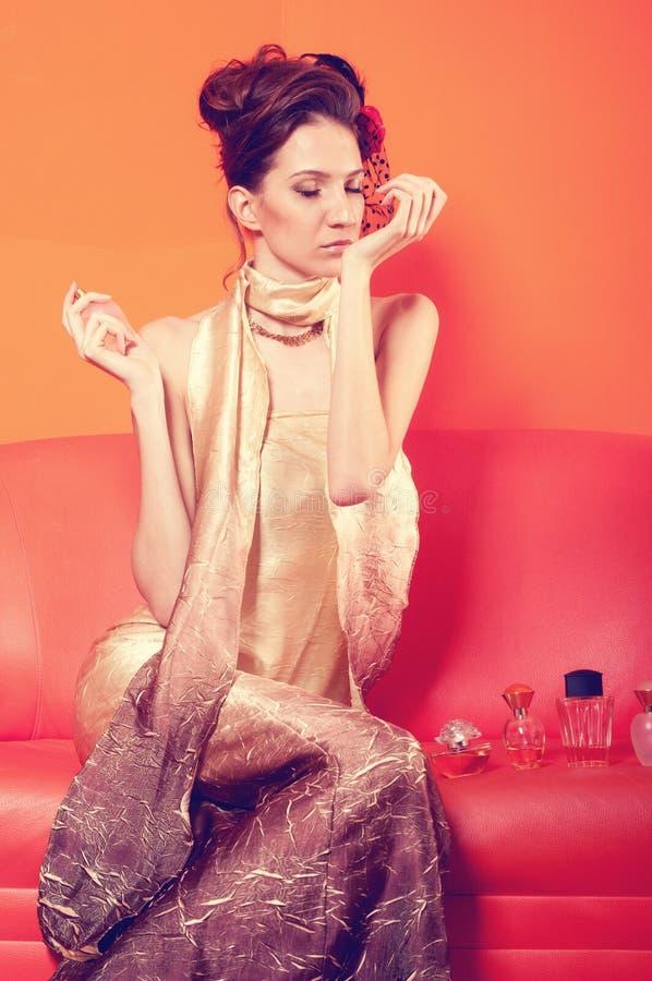 Señora elegante hermosa que prueba perfumes en el sofá imagenes de archivo