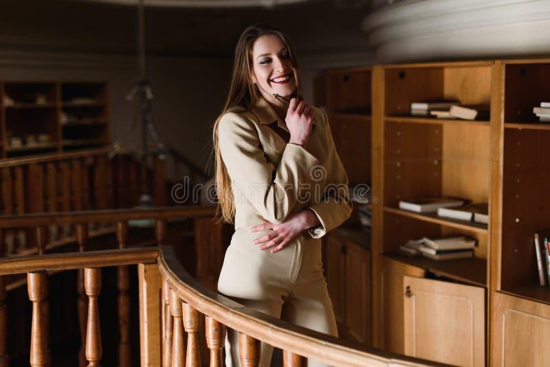 Señora elegante joven hermosa que presenta en la biblioteca del vintage imágenes de archivo libres de regalías