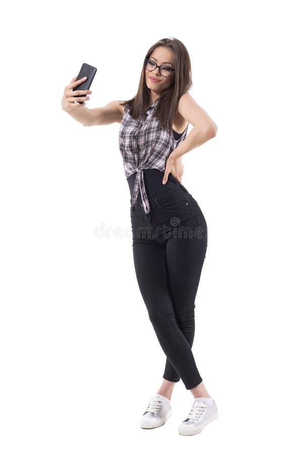 Señora elegante preciosa joven linda con los vidrios que toman la foto del selfie que mira el teléfono móvil imágenes de archivo libres de regalías