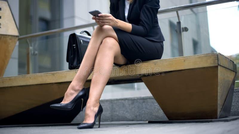 Señora elegante que se sienta en banco, escribiendo el mensaje en smartphone, para cliente que espera imágenes de archivo libres de regalías