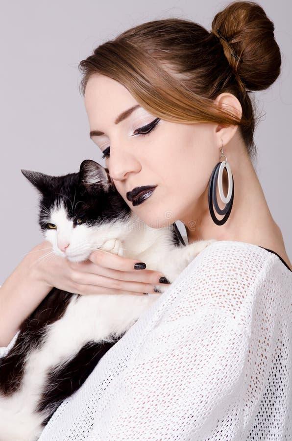 Señora elegante que sostiene el gato blanco y negro con los ojos amarillos imagenes de archivo