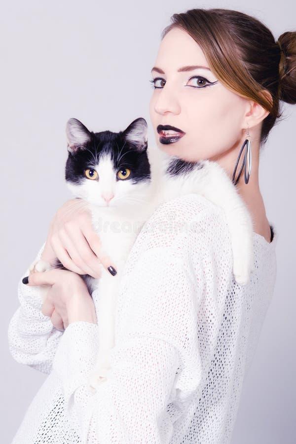 Señora elegante que sostiene el gato blanco y negro con los ojos amarillos fotografía de archivo