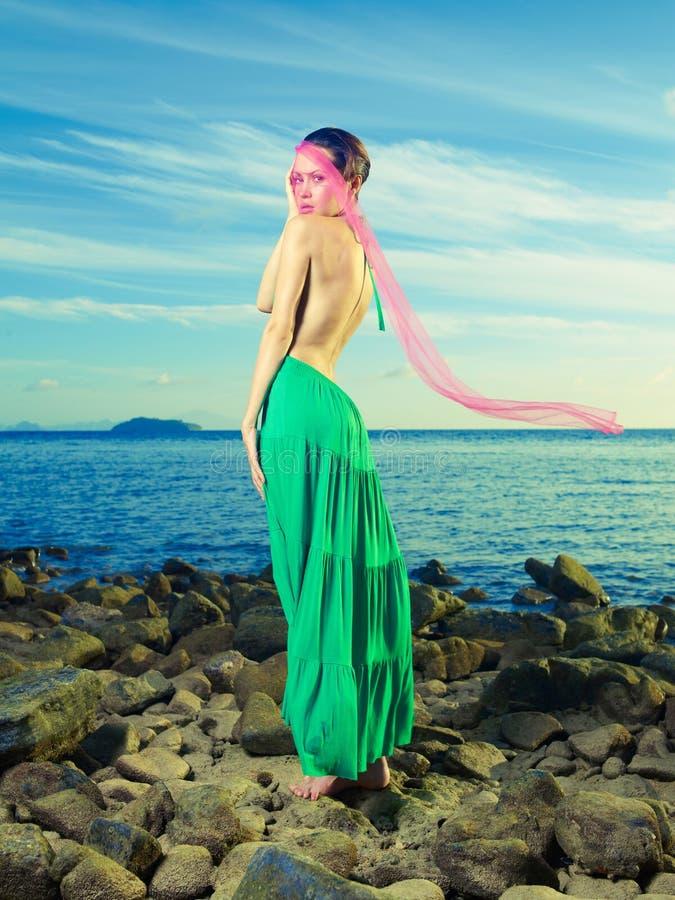 Señora en alineada verde en la costa imagen de archivo