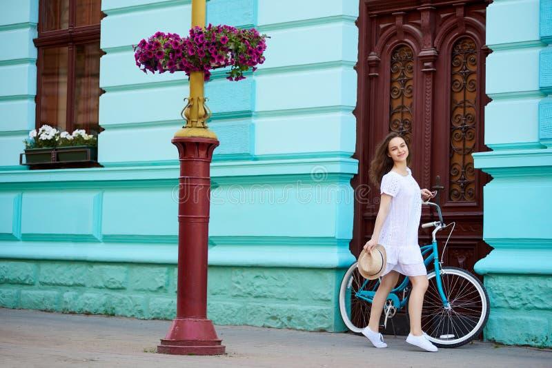 Señora en ciudad vieja con la bicicleta retra contra puerta del vintage imagenes de archivo