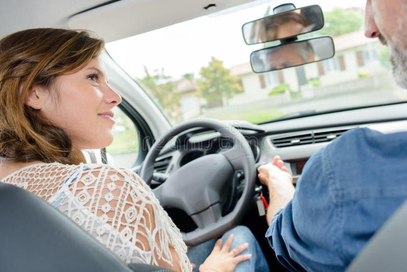 Señora en coche del asiento de conductores que escucha el hombre imagenes de archivo