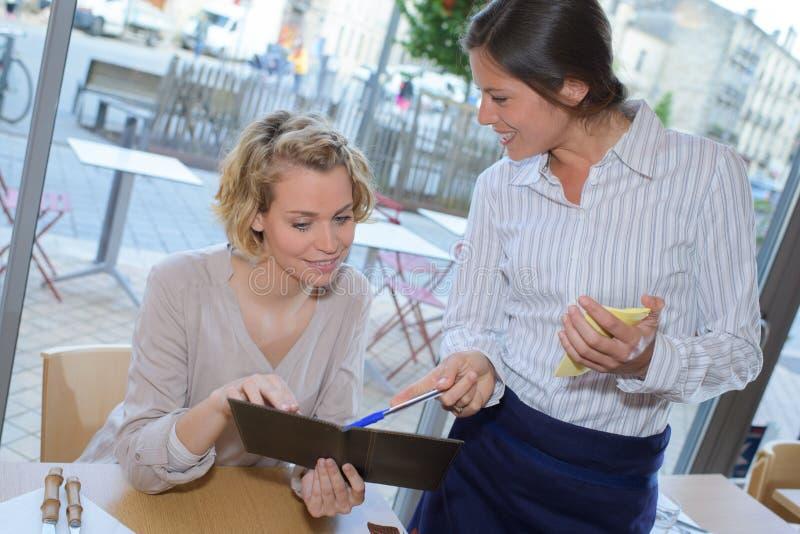 Señora en el café que mira el menú con la camarera fotografía de archivo