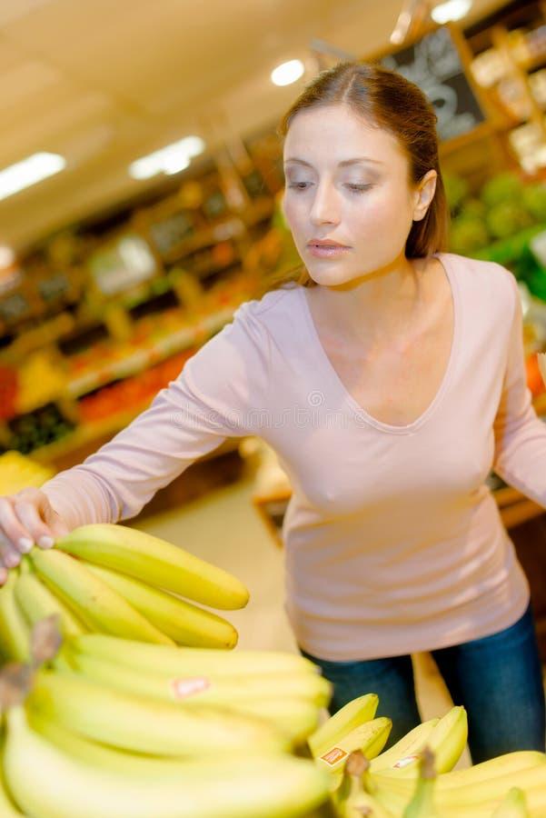 Señora en el supermercado que elige plátanos imagenes de archivo