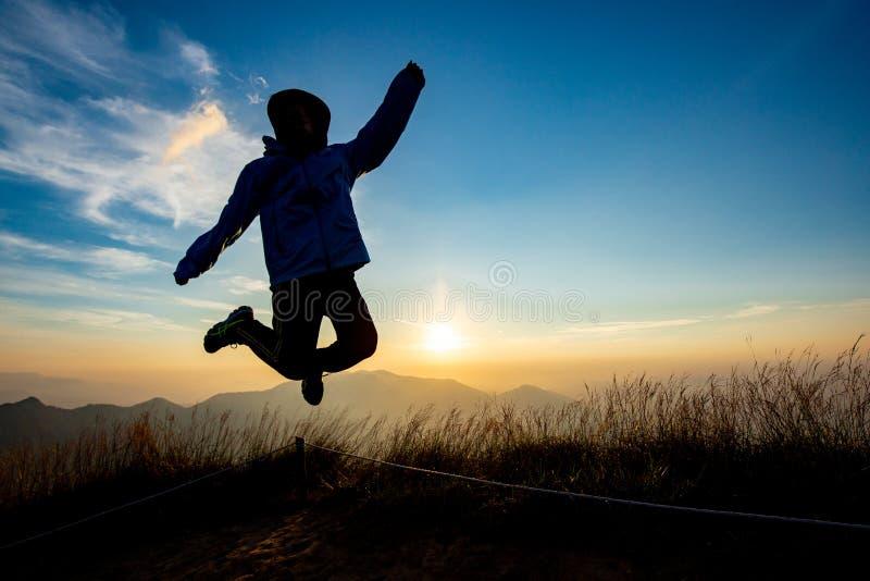 Señora en la acción del salto con el fondo de la puesta del sol imagen de archivo