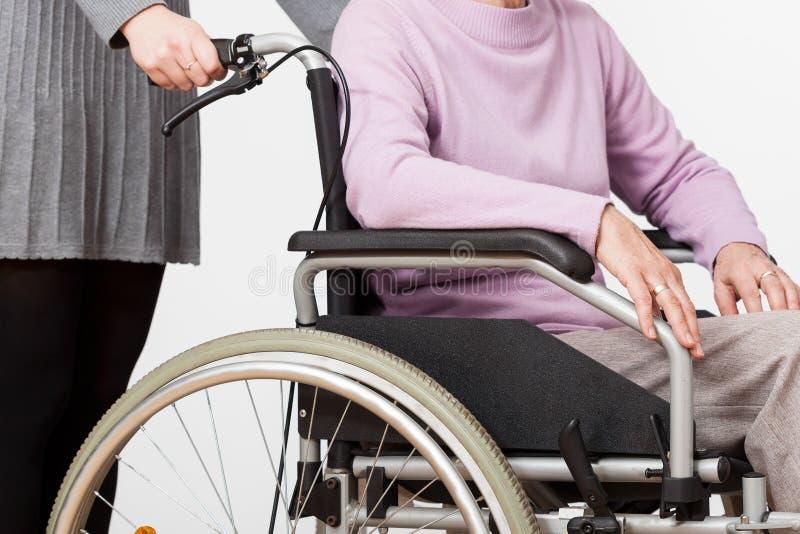 Señora en la silla de ruedas y su guarda imagen de archivo