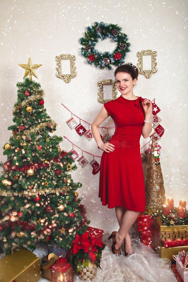 Señora en vestido rojo entre la decoración de la Navidad fotografía de archivo