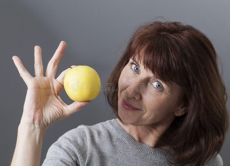 Señora envejecida centro que nos presenta un poco de fruta fotografía de archivo libre de regalías