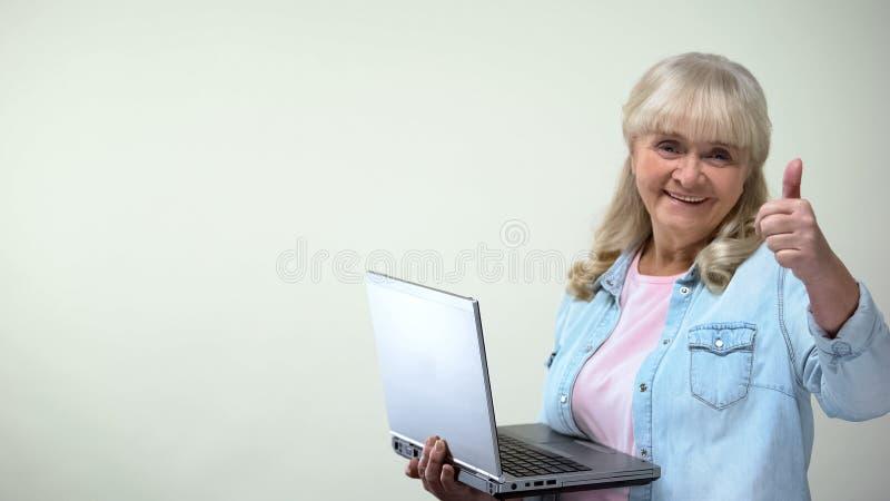 Señora envejecida usando el ordenador portátil que muestra los pulgares-para arriba, conocimiento de informática para los pens imagen de archivo