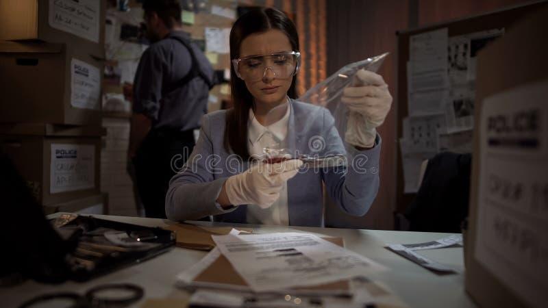 Señora experta que examina el cuchillo sangriento de la escena de asesinato, científico profesional fotografía de archivo libre de regalías