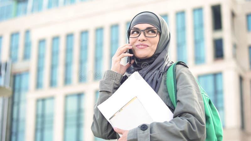 Señora feliz en hijab musulmán que habla en el teléfono, llevando a cabo documentos a disposición, campus imagen de archivo
