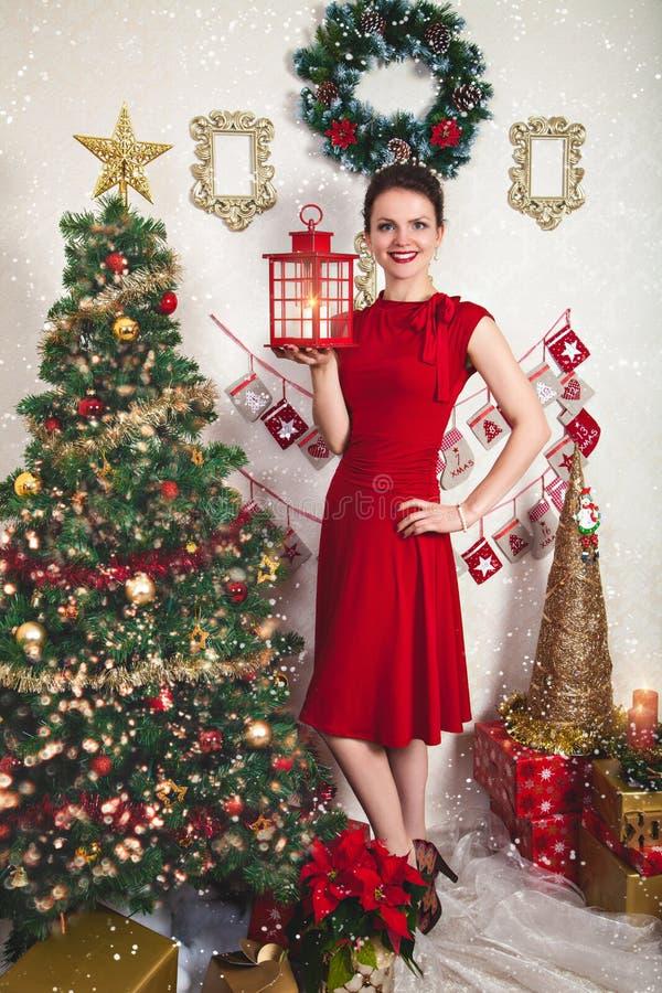 Señora feliz joven en vestido rojo con la linterna de la Navidad fotografía de archivo