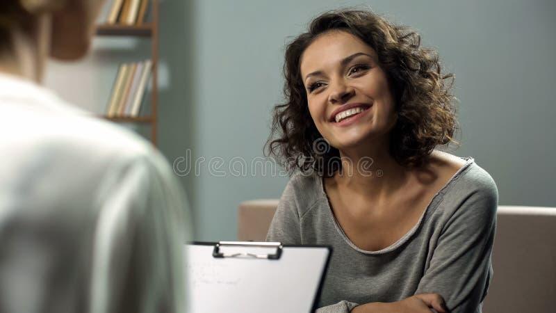 Señora feliz joven que habla con el psicólogo en la clínica, sesión de la terapia de la rehabilitación fotografía de archivo libre de regalías