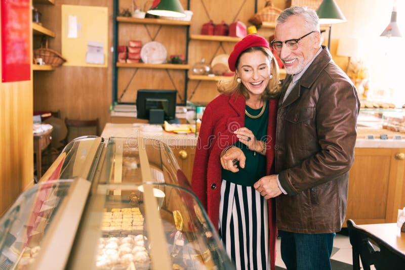 Señora francesa hermosa que elige el postre que viene a la cafetería con el marido fotografía de archivo libre de regalías