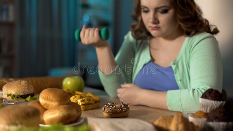 Señora gorda que ejercita y que mira tristemente la comida basura, problema de la obesidad fotografía de archivo