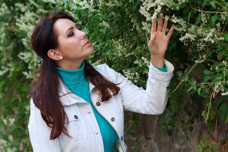 Señora hermosa al lado de una planta floreciente fotos de archivo libres de regalías